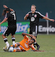 Houston Dynamo midfielder Ricardo Clark (13) slides to tackle the ball from DC United midfielder Fred (7)  ,The Houston Dynamo defeated DC United 3-1 to secure their place in  the SuperLiga semifinals, at RFK Stadium in Washington DC, Saturday July 19, 2008.