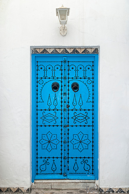 An ornate blue door in the town of Sidi Bou Said. The town is located about 20 km from the capital, Tunis. Named after a religious figure who lived there, Abou Said ibn Khalef ibn Yahia Ettamini el Beji. It is popular with tourists due to its extensive use of blue and white in its architecture. It also has a reputation as a town of artists.
