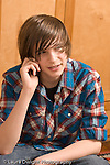 Teenage boy 14 years old closeup talking on cell telephone vertical Caucasian