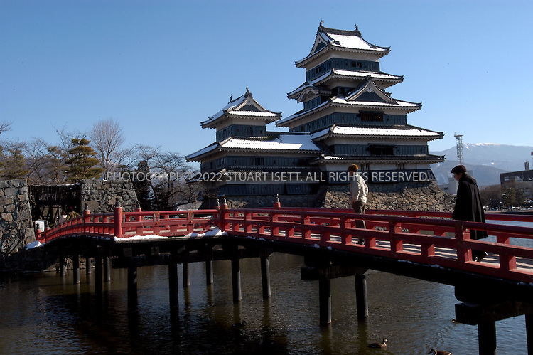 December 14, 2002, Matsumoto, Japan: The red foot bridge leading into Matsumoto Castle. Unlike European castles, which are usually made of stone, Matsumoto's 98 foot tall structure, one of four Japanese castles officially designated as National Treasures, is almost entirely made of wood. The building can be seen from almost anywhere in the central city, which makes finding it simple.  Photograph by Stuart Isett ©2002 Stuart Isett All rights reserved. Credit: Stuart Isett / Polaris