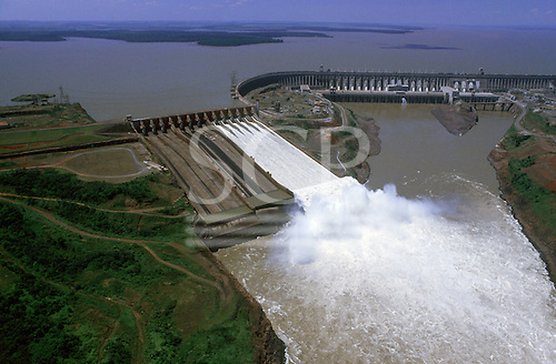 Parana State, Brazil. Aerial view of the Itaipu Hydroelectric Dam with open flood gates and reservoir.