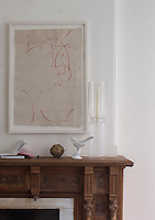 A framed drawing by Elliott Puckette hangs above the original wood fireplace in the dining room