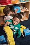 Education Preschool toddler 2s program Head Start boy making stack of cardboard blocks, another boy playing in background