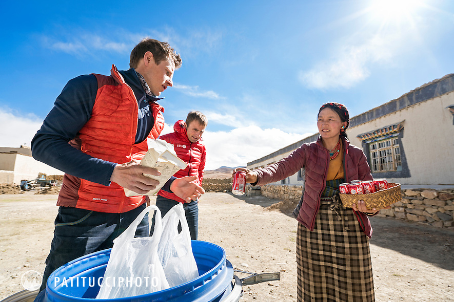 While packing for their climbing expedition to the 8000 meter peak Shishapangma, Tibet, a local woman offers a coke to Ueli Steck and David Göttler