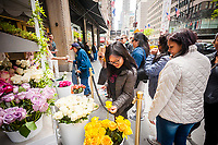 "A cart outside of Saks Fifth Avenue in New York distributes roses to passer-by for Mother's Day as part of Saks' ""Glam Gardens"" promotion, seen on Friday, May 12, 2017. The ""Glam Gardens"" promotion is a collaboration between the department store and a number of their beauty products suppliers creating exclusive products for Saks, just in time for Mother's Day. (© Richard B. Levine)"