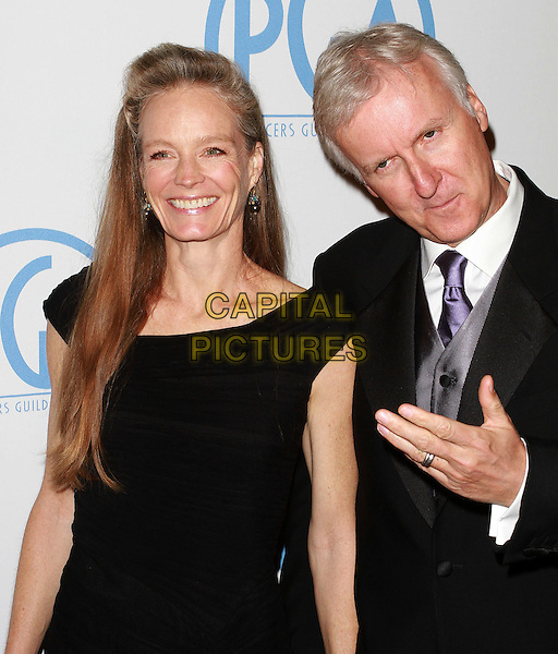 SUZY AMIS & JAMES CAMERON .22nd Annual Producers Guild Awards held At The Beverly Hilton Hotel, Beverly Hills, CA, USA, 22nd January 2011..half length black dress suit tie hand smiling gesture  couple husband wife purple .CAP/ADM/KB.©Kevan Brooks/AdMedia/Capital Pictures.