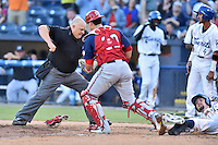 Hagerstown Suns catcher Jorge Tillero (30) tags out Chris Keck (16) of the Asheville Tourists as home plate umpire Andy Glenn prepares to make a call during a game against the Asheville Tourists at McCormick Field on June 8, 2016 in Asheville, North Carolina The Tourists defeated the Suns 10-8. (Tony Farlow/Four Seam Images)