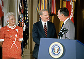United States President George H.W. Bush and first lady Barbara Bush present the Presidential Medal of Freedom to US Secretary of State James A. Baker, III, during a ceremony in the East Room of the White House in Washington, DC on July 3, 1991. Secretary Baker is being honored for his efforts to ensure the success of Operation Desert Shield / Operation Desert Storm and the liberation of Kuwait.<br /> Credit: Ron Sachs / CNP