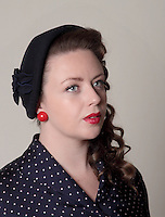 woman photographed in vintage dress, wearing a blue dress whit white dots, red earrings and a blue hat, with a flower.