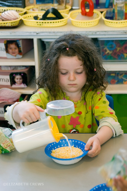 Berkeley CA  Four-year-old practicing pouring on her snack-time cereal at preschool