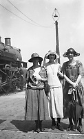 Three women in 1930's attire wait by a train.  (photo: www.bcpix.com)