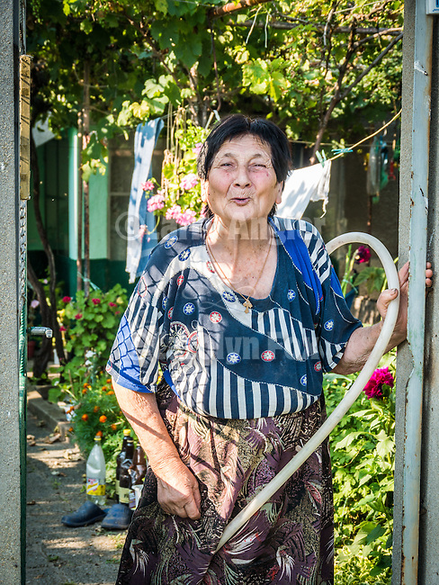 A woman stands at her gate as she waters her garden, Miekarovo, Bulgaria