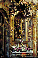 Interior of Asam Church with opulent statue of Mary and cherubs set in niche; profuse ornamentation; flowers and candles on stone table; large lit candle. Munich Bavaria Germany.