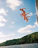 FIJI, Northern Lau Islands, young women jump off the top of a yacht into the South Pacific Ocean