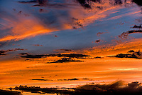 Clouds near horizon with strong color shift from sunset effect and areas of dark cloud providing a moody feel