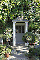 The exterior of the house is hidden behind a covering of ivy and Hobelia while the small door has been given a grand portico entrance