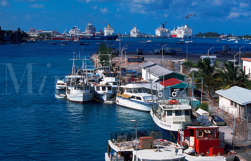 Nassau main harbor with fishing boats in foreground and larger ships in background. Nassau, Bahamas.