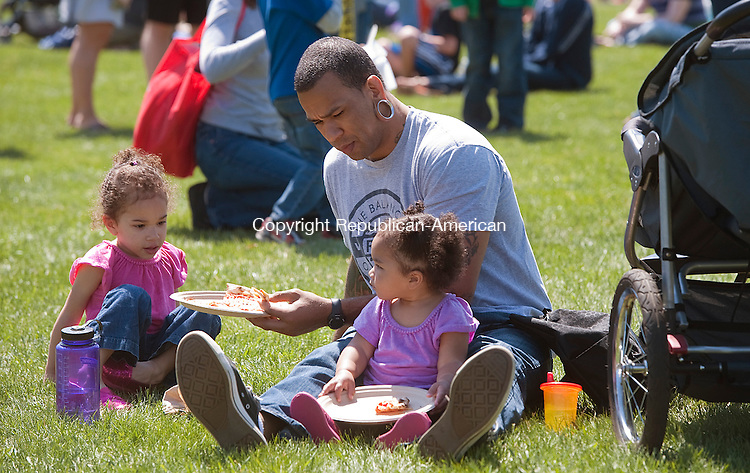 WOODBURY, CT 27 APRIL 2013--042713JS22--FOR COUNTRY LIFE USE ONLY-- Josh Owen of Waterbury enjoys lunch with his daughters Corinne Owen, 3, left, and McKenzie, 1, during the 19th annual Earth Day celebration at Hollow Park in Woodbury. The nonprofit event sponsored in part by New Morning Market, included entertainment and local, natural and organic vendors and exhibitors. Any proceeds raised during the event will be donated to local charities. .Jim Shannon Republican-American.