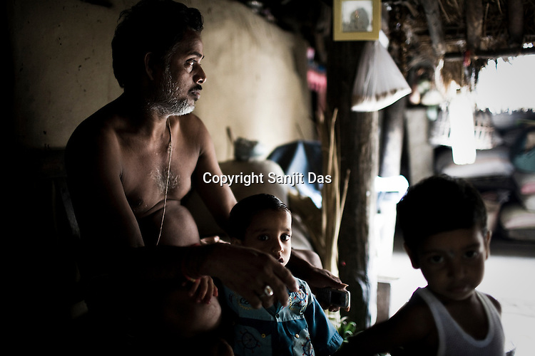43 year old Suresh Kumar Dash is seen with his grandchildren in his hut in village Dhinkhia, in Orissa, India. Proposed steel project would displace all families of this village so they are determined not to leave their soil. If the plant is constructed, the villagers from Dhinkia will be the first ones to be displaced.