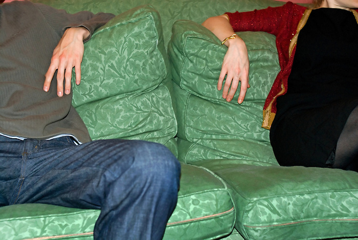 A young man and a young woman sit apart on a green sofa.