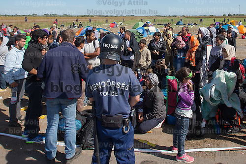 Police officer stands guard at a collection point of illegal migrants near Roszke (about 174 km South of capital city Budapest), Hungary on September 07, 2015. ATTILA VOLGYI