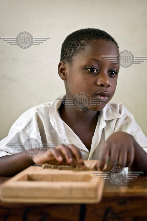 A blind child reads braille at a school for children and young people with disabilities. The school is supported by NGO Terre Des Hommes..