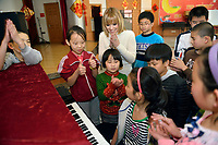 """Swiss singer and TV presenter Francine Jordi listens a student playing piano while visiting """"SOS Kinderdorf"""" in Tianjin, China. 22-Mar-2016"""