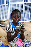 BURKINA FASO, Provinz Poni, Gaoua, weekly market with food crops and solar panels, girl playing with mobile phone /Gaoua, Markt, Verkauf Nahrungsmittel, Stand mit Solar Modulen, Maedchen mit Mobiltelefon
