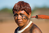 Xingu Indigenous Park, Mato Grosso State, Brazil. Aldeia Waura. Payapakuma Feather earplugs and snake design genipapo facepaint..