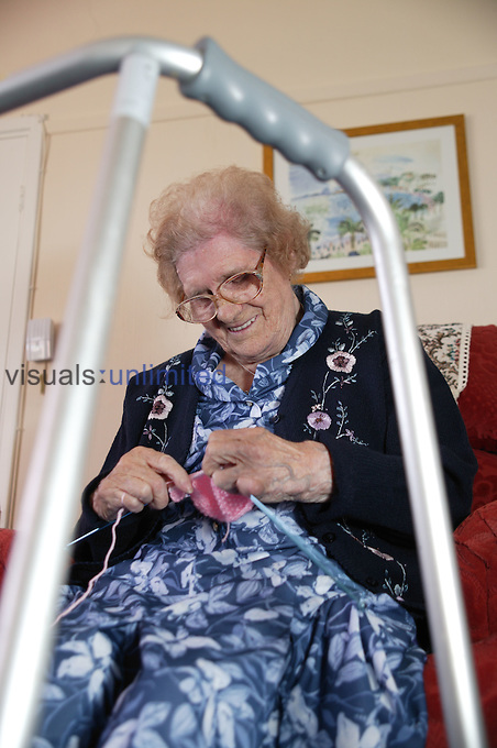 View through a walking frame of an elderly woman knitting at home. MR