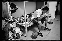 A basketball player of Dongguan Guangming Middle School in Dongguan, Guangdong province, eats dinner at his dormitory after an evening training session, November 2011.