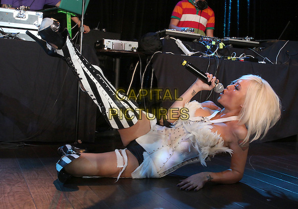 TILA TEQUILA .Tila Tequila Album Release party Performance held At The Conga Room, Los Angeles, California, USA, .12th May 2010..music performing performance on stage concert gig full length white strapless corset top ruffle skirt dress black striped otk knee thigh high boots lace-up heels  hand knickers hotpants tattoo microphone singing  leg kicking lying down on floor  feathers feather .CAP/ADM/KB.©Kevan Brooks/AdMedia/Capital Pictures.
