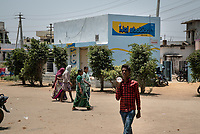 Pedestrians walk past the iJal station in Medak District Hospital in Medak, Telangana, India.