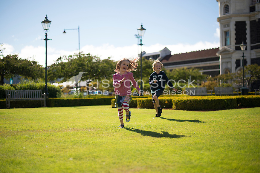 Little girl playing on green grass outside the Dunedin Railway Station, (running towards camera), on a sunny day, Otago, South Island, New Zealand - stock photo, canvas, fine art print