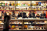 ITALY, Venice. Patrons at a shop enjoying Pastries and drinks at night.