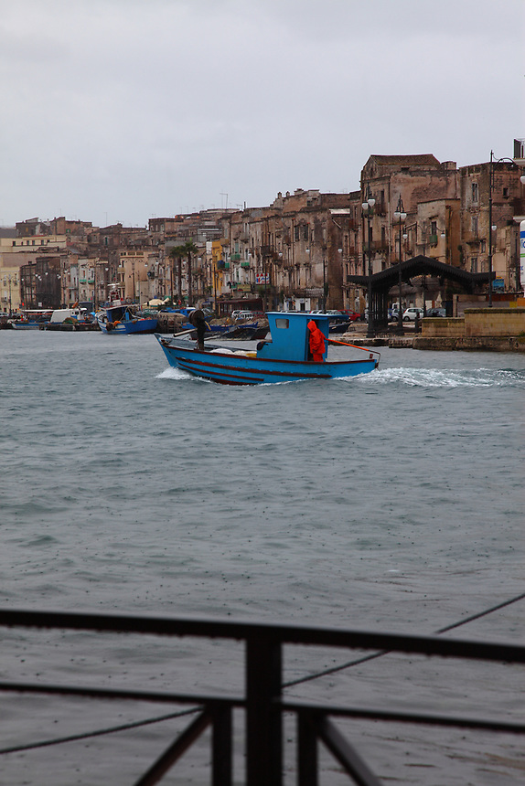 Taranto: A view from a bridge of a part of the port. The small blue boat in the center, with a person covered by a red raincoat is enhanced by the grey water and the cloudy sky. On the background, a beautiful view of a part of the old town.