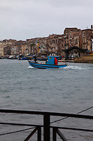 A view from a bridge of a part of the port of Taranto. The small blue boat in the center, with a person covered by a red raincoat is enhanced by the grey water and the cloudy sky. On the background, a beautiful view of a part of the old town. Digitally Improved Photo.