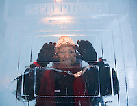 Sweden, SWE, Kiruna, 2006-Apr-12: A woman standing in a phone cabin made of ice in the Jukkasjarvi icehotel.