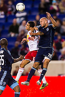 Tim Cahill (17) of the New York Red Bulls goes up for a header with Aurelien Collin (78) of Sporting Kansas City. The New York Red Bulls and Sporting Kansas City played to a 0-0 tie during a Major League Soccer (MLS) match at Red Bull Arena in Harrison, NJ, on October 20, 2012.