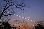 The setting sun highlights the contrails of two jet planes passing overhead.