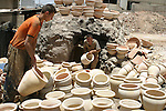 Palestinian pottery worker takes out the fired potteries out of a stove at his workshop at a pottery workshop in the West Bank city of Hebron on June 30, 2009. Pottery is a very ancient and traditional industry in Hebron. It has been known since more than 2000 years ago. However, nowadays this industry is almost wiping out as a result of the increased violence in the region over the last two years, the pottery factory output has been reduced by almost two thirds. Photo by Najeh Hashlamoun