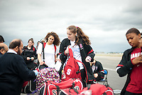 SAN JOSE, CA--Freshman Bonnie Samuelson drops her bags on the tarmac for planeside inspection at Atlantic Aviation en route to Norfolk, VA for the first and second rounds of the 2012 NCAA tournament.