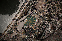 """November 12, 2014 - Tawergha City, Libya: The cover of Gaddafi's """"Green Book"""" is seen among the detritus of a school classroom in Tawergha City ghost town after heavy clashes occured during 2011 war in Libya when Tawerghans were forced to move from their city home as they were harassed by the armed militias of Misrata during the uprising against Colonel Gaddafi. (Photo/Narciso Contreras)"""