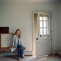 A portrait of designer Edwina Hunt sitting in the entrance hall of her home