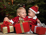 Two year old girl and an eight month old boy sharing gifts under a Christmas tree