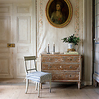 Detail of a distressed wooden chest of drawers and a painted chair in the master bedroom of this Swedish country house