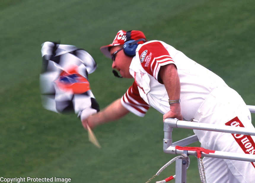 The NASCAR flag man waves the green flag during qualifying for the Daytona 500 in February 2000. (Photo by Brian Cleary)