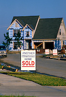 Exterior view of new home under construction with a real estate 'Sold' sign in front.