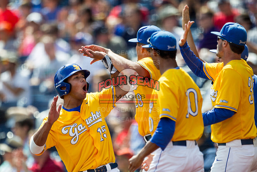 UC Santa Barbara Gauchos outfielder Devon Bradford (15) is greeted by his teammates after scoring against the Miami Hurricanes in Game 5 of the NCAA College World Series on June 20, 2016 at TD Ameritrade Park in Omaha, Nebraska. UC Santa Barbara defeated Miami  5-3. (Andrew Woolley/Four Seam Images)