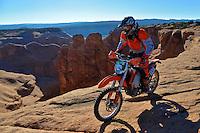 Backcountry rider skirts a canyon rim near Moab, Utah. October 2012.